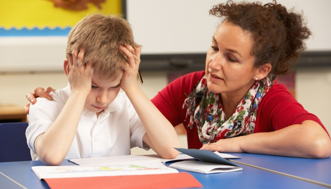 Stressed Schoolboy Studying In Classroom With Teacher